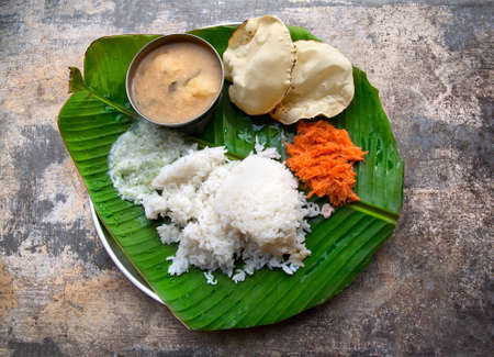 Homemade Indian vegetarian rice, sambar, grated carrot and poppadoms on the banana leaf at grunge background