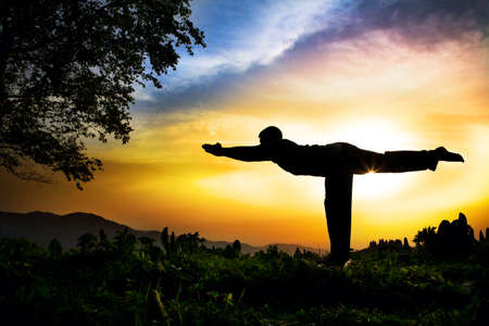 Man silhouette doing virabhadrasana III warior pose with tree nearby outdoors at sunset background