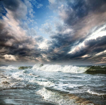 Ocean with waves and dramatic blue sky with clouds