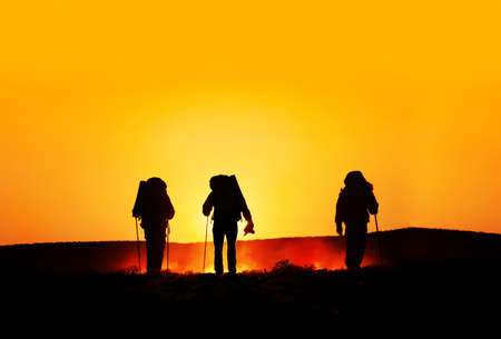 Three tourist silhouettes walking on the hills with track sticks and backpacks at sunset orange background. Free space for text, good template for web design