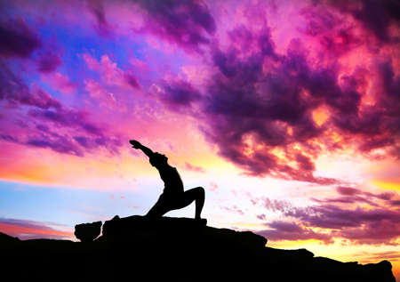 Yoga virabhadrasana I warrior pose by man silhouette with purple dramatic sunset sky background. Free space for text and can be used as template for web-site