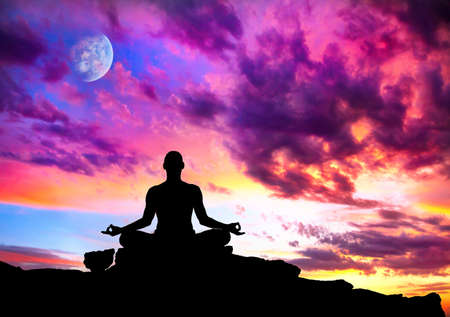 Yoga meditation in lotus pose by man silhouette with moon and purple dramatic sunset sky background. Free space for text and can be used as template for web-site