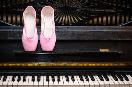 Pink pointe on the black old piano