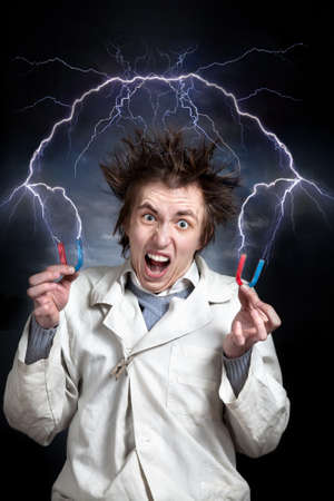 Crazy young professor with magnets in white coat. Thunder strikes from magnets around him