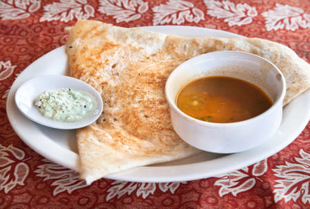 Indian traditional vegetarian masala dosa with potato inside, sambar and coconut chutney nearby at Indian restaurant