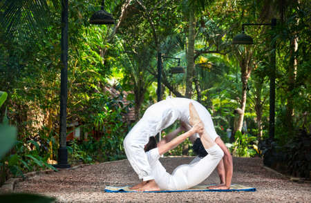 Couple Yoga of man doing chakrasana and woman doing dhanurasana poses in white cloth in the garden. Represents yin and yang