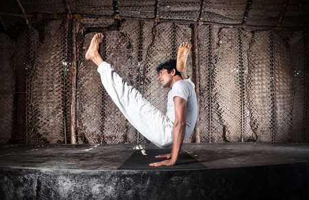 Yoga chakorasana pose by Indian man in white cloth in yoga shala, Varkala, Kerala, India