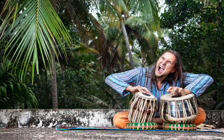 Man playing on traditional Indian tabla drums at tropic background