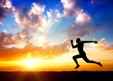Photo pour Silhouette of man running towards the sun at cloudy background - image libre de droit