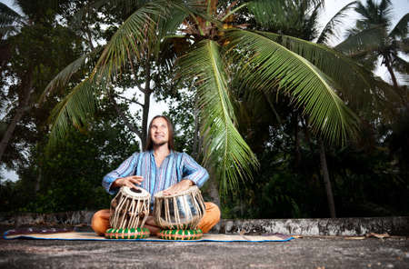 Happy man is playing on traditional Indian tabla drums at tropical palms background