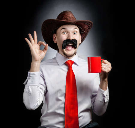 Funny Cowboy with big moustache showing OK gesture and holding red cup at black background