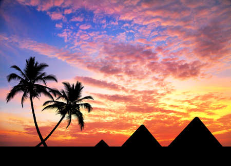 Egyptian Pyramids and palm trees in silhouette at orange sunset sky