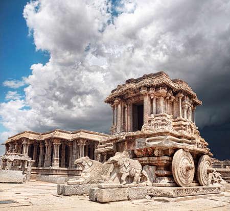 Stone chariot in courtyard of Vittala Temple at blue overcast sky in Hampi, Karnataka, India