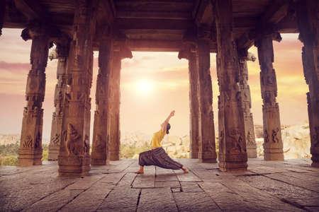 Woman doing yoga in ruined ancient temple with columns, Hampi, Karnataka, India