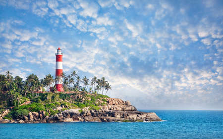 Photo pour Lighthouse on the rocks near the ocean at blue sky with clouds in Kovalam, Kerala, India   - image libre de droit