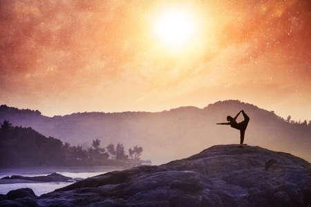 Photo pour Woman doing Yoga natarajasana dancer pose on the rocks at sunset at Om beach, Gokarna, India - image libre de droit