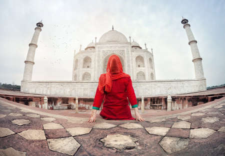 Woman in red costume sitting on the floor and looking at Taj Mahal in Agra, Uttar Pradesh, India