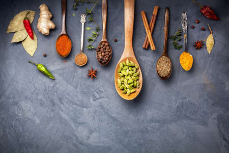 Various Spices like turmeric, cardamom, chili, bayberry, bay leaf, ginger, cinnamon, cumin, star anise on grunge background with space for your text