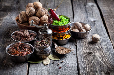 Photo pour Spices, pepper grinder, spoon with seeds at grey wooden background - image libre de droit