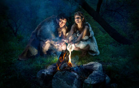 Photo pour Cave people dressed in animal roast oneself at bonfire in the forest - image libre de droit