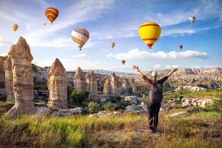 Young woman with backpack looking to sunrise sky full of hot air balloons with raised hands in Cappadocia, Turkey