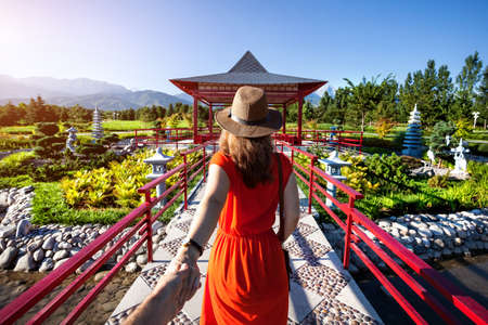 Photo pour Woman in orange dress and hat holding man by hand going to Japanese Garden with pagoda - image libre de droit