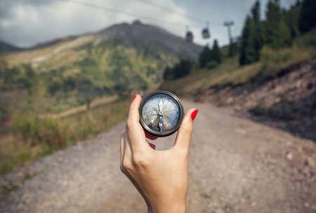 Foto de Hand of woman tourist with vintage compass at mountain road - Imagen libre de derechos