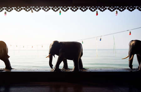 Photo pour Wooden elephant statues decoration of resort at tropical beach at sunrise - image libre de droit