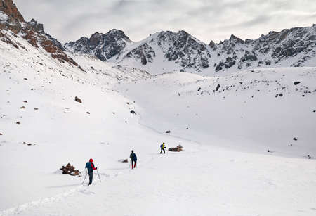 Photo pour Three tourists on the snow trail climb the mountains - image libre de droit