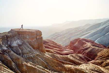Foto de Silhouette of runner athlete on the big rock in canyon with red desert mountains - Imagen libre de derechos