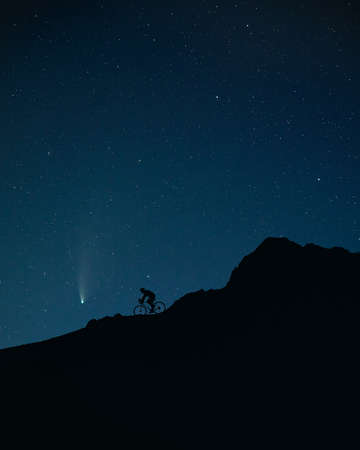 Photo for Silhouette of man riding the bicycle at the mountains under night sky with stars and Neowise comet. - Royalty Free Image