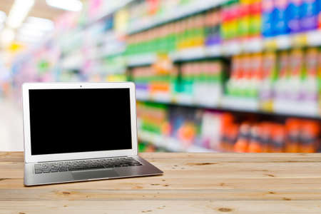 Laptop with blank screen on Wood table and Supermarket blur background, Product display, template, business concept
