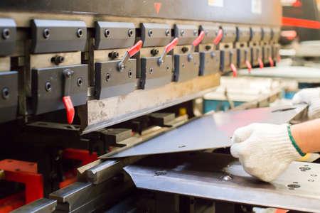 worker in factory at metal skip machine putting work piece in
