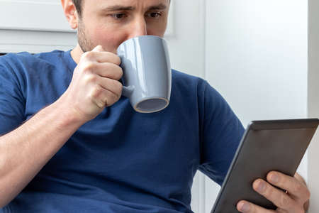 Foto de A man in a blue t-shirt holds the gray cup with one hand, drinking from it, and holds the electronic book with the other hand. Reading an e-book or news on a tablet at breakfast. Selective focus - Imagen libre de derechos