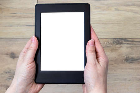 Photo for A modern black electronic book with a white blank screen in female hands against a blurred wooden tile floor background. Mockup tablet closeup - Royalty Free Image