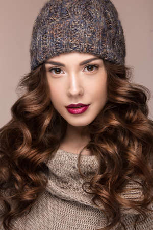 Beautiful girl with a gentle make-up, curls  in winter brown knit cap. Warm winter image. Beauty face. Picture taken in the studio.