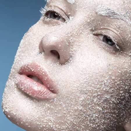 Portrait of a girl with pale skin and sugar snow on her face. Creative art beauty fashion. Picture taken in the studio on a blue background.の写真素材