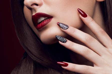 Photo pour Pretty girl with unusual hairstyle, bright makeup, red lips and manicure design. Beauty face. Art nails. Studio portrait - image libre de droit