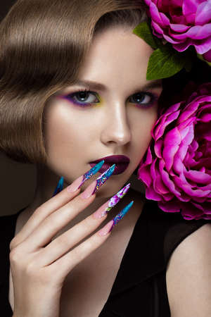 Foto de Beautiful girl with colorful make-up, flowers, retro hairstyle and long nails. Manicure design. The beauty of the face. Photos shot in studio - Imagen libre de derechos