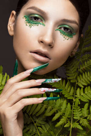 Photo pour Beautiful girl with art make-up, fern leaves and long nails. Manicure design. The beauty of the face. Photos shot in studio - image libre de droit