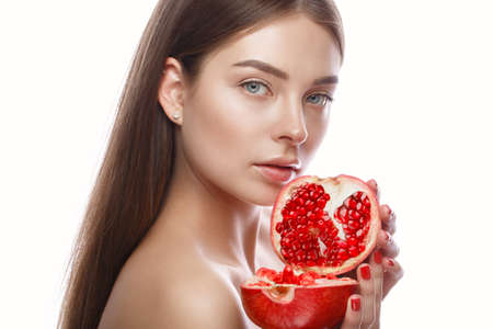 Foto de Beautiful young girl with a light natural make-up and perfect skin with pomegranate in her hand. Beauty face. Picture taken in the studio on a white background. - Imagen libre de derechos