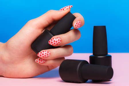 Foto de Black bottles of nail polish on a colorful background. Manicure design - Imagen libre de derechos