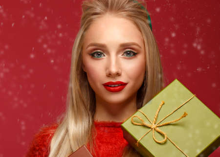 Photo pour Beautiful blonde girl in a New Years image with boxes of gifts in hands. Beauty face with festive makeup. Photo taken in the studio. - image libre de droit