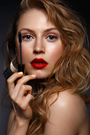 Photo pour Beautiful girl with red lips and classic makeup and curls with mascara in hand. Beauty face. Photo taken in the studio. - image libre de droit
