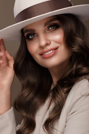 Photo pour Beautiful sexy woman in a fashionable hat, with classic make-up, wave hair and smile. Beauty face. Photo taken in the studio. - image libre de droit