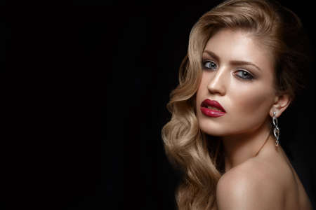 Photo pour Beautiful girl with red lips and classic makeup and curls. Beauty face. Photo taken in the studio. - image libre de droit