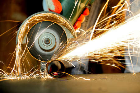 Photo for Worker cutting metal with grinder. Sparks while grinding iron - Royalty Free Image