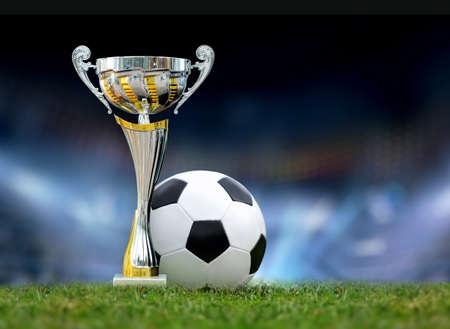 Golden trophy in grass on soccer field background
