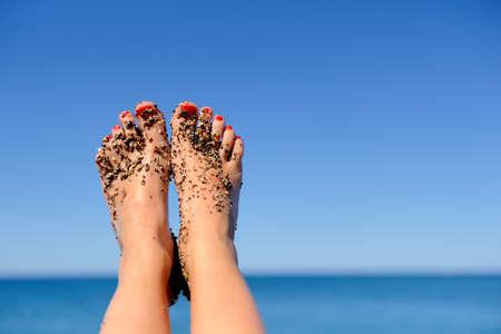 Foto de Vacation holidays. Woman feet closeup of girl relaxing on beach - Imagen libre de derechos