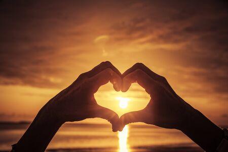 Photo pour Hand shaped heart at sunset by the sea - image libre de droit